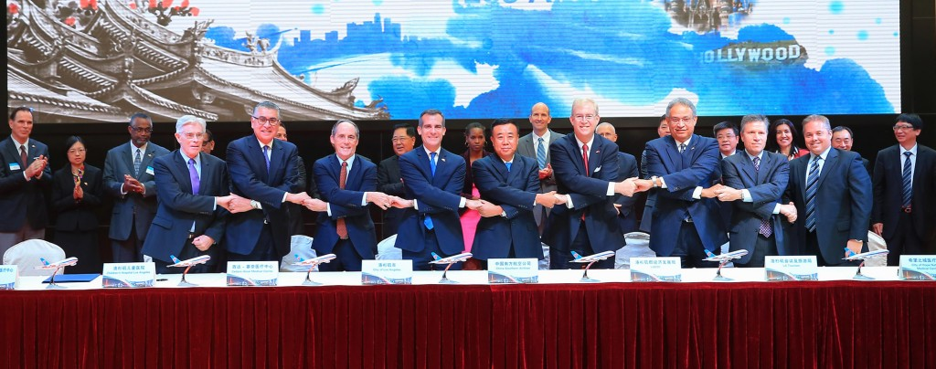 Delegates join hands to celebrate signing historic MOU for medical travel from China to LA area medical centers. (L to R) Thomas Coates (UCLA Health), Rich Cordova (Children's Hospital), Tom Priselac (Cedars-Sinai), Mayor Eric Garcetti, Chairman Si (China Southern), Bill Allen (LAEDC) Ernest Wooden (LA Tourism), Harlan Levine (City of Hope) and Scott Evans (Keck Medicine at USC)   -Nov 17, 2014